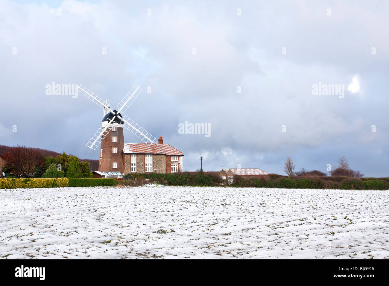 Weybourne windmill in Norfolk following winter snow showers - Stock Image