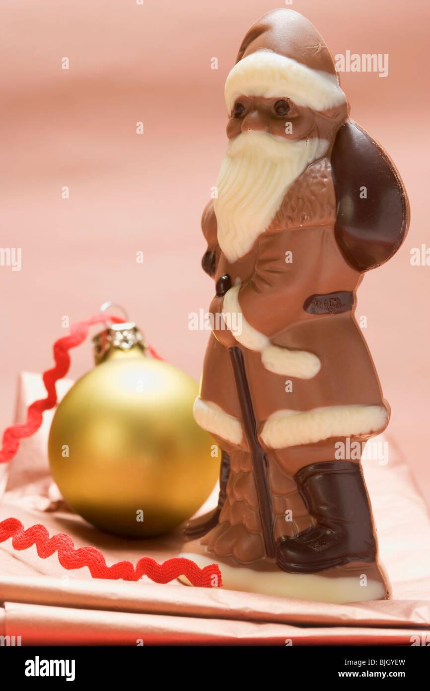 Chocolate Father Christmas beside Christmas bauble - - Stock Image