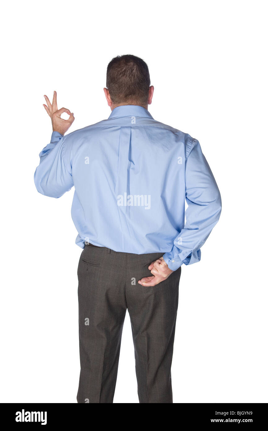 A businessman giving the okay signal has his fingers crossed behind his back as if being a liar or deceiving his - Stock Image