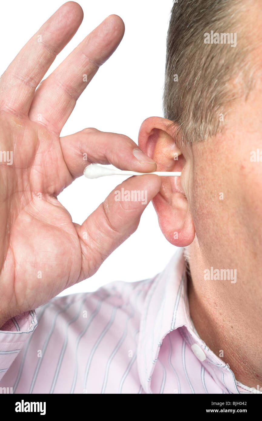 A man cleans his ear with a cotton swab for good hygiene. - Stock Image