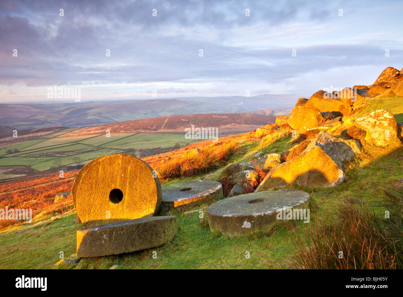 Abandoned millstones beneath Stanage Edge at first light in the Peak District National Park Stock Photo