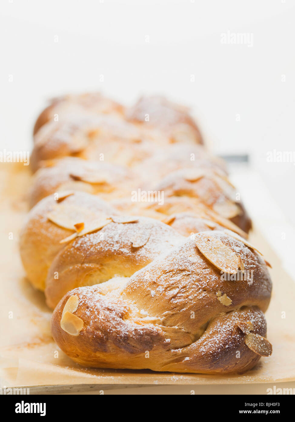 Bread plait with flaked almonds & icing sugar on baking parchment - - Stock Image