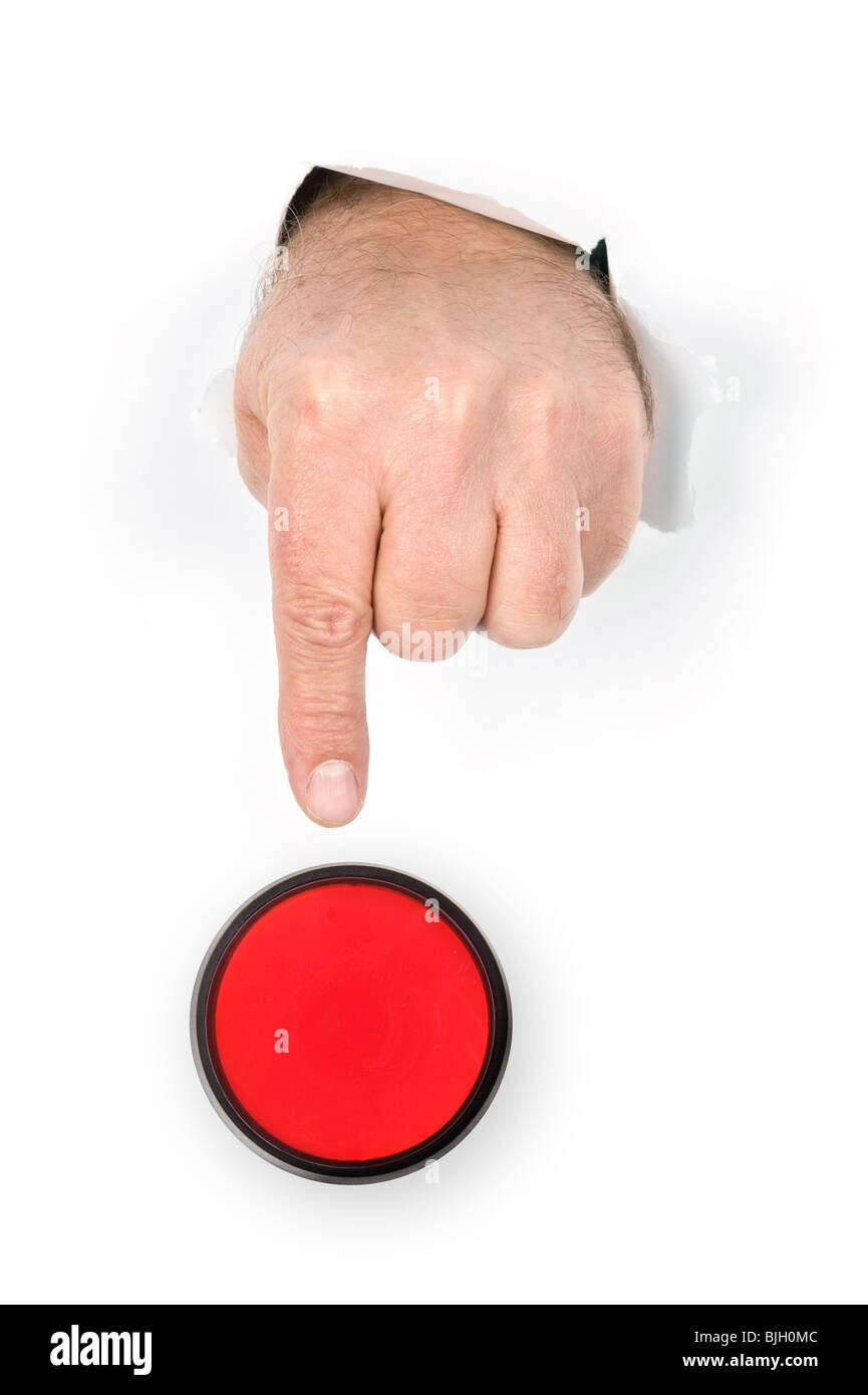 A hand with index finger extended pokes through torn paper prepares to push the panic stop button. - Stock Image