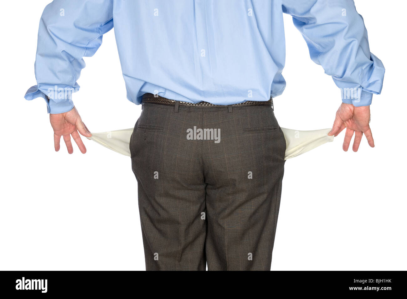 A businessman holds out his empty pockets showing he is broke and has no cash. - Stock Image