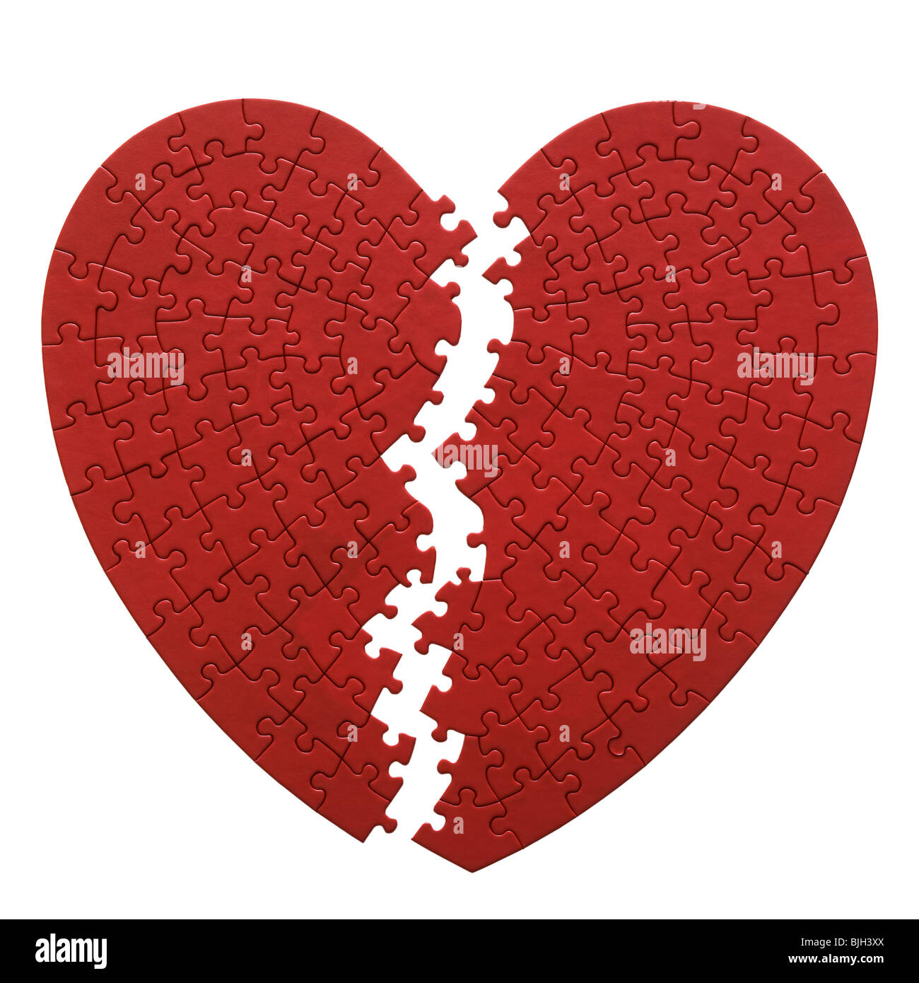 red heart shaped jigsaw puzzle on a white background - Stock Image