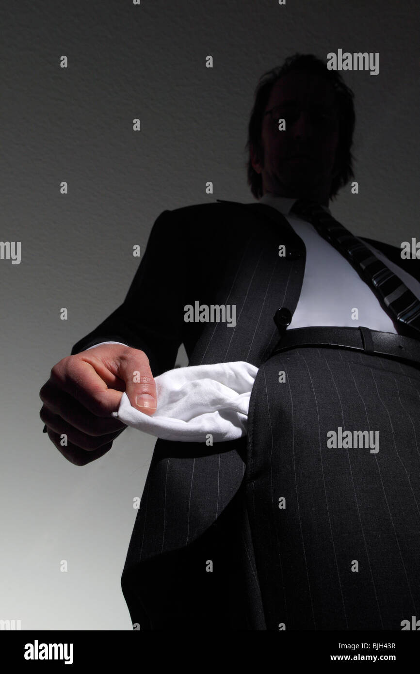 Man in a suit with empty pockets. Symbol: insolvency, national bankruptcy, etc. - Stock Image