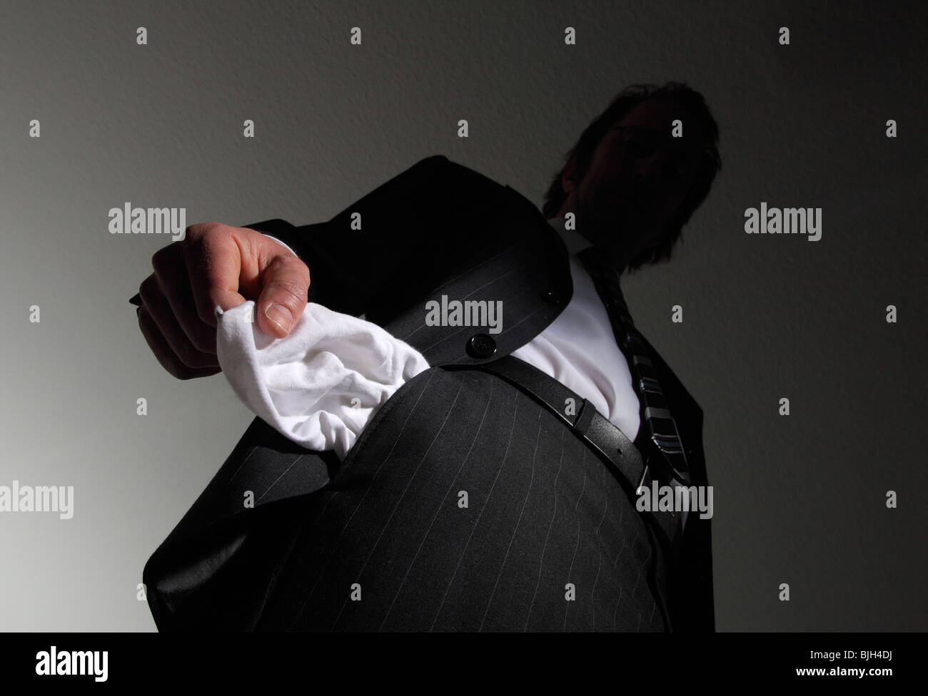 Man in a suit with empty pockets. Symbol: insolvency, national bankruptcy, etc - Stock Image