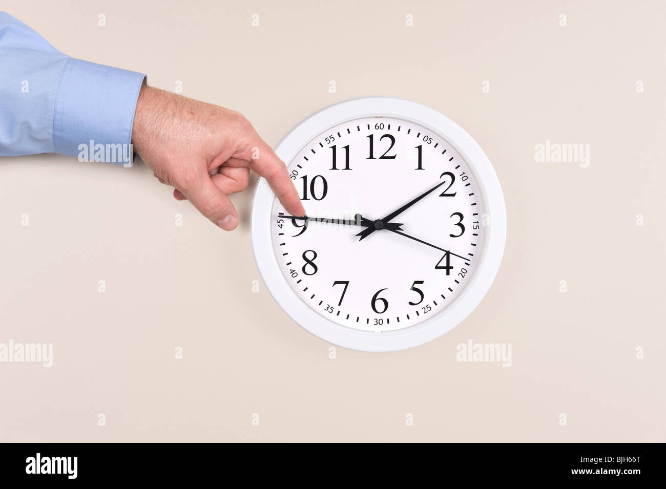 A man uses his finger to push back the time on a clock to daylight savings time - Stock Image