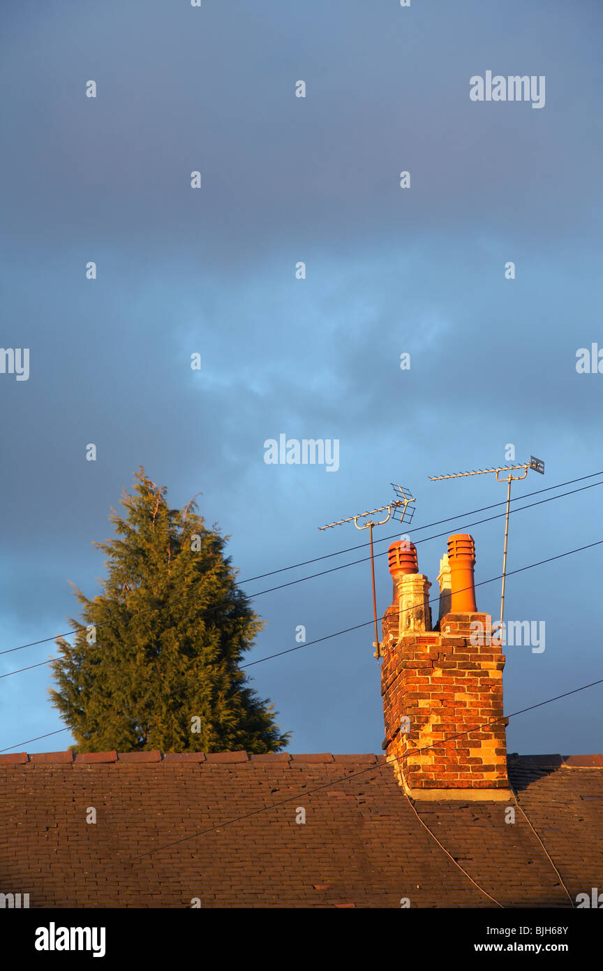 Chimney with aerials in late afternoon light with clouds - Stock Image