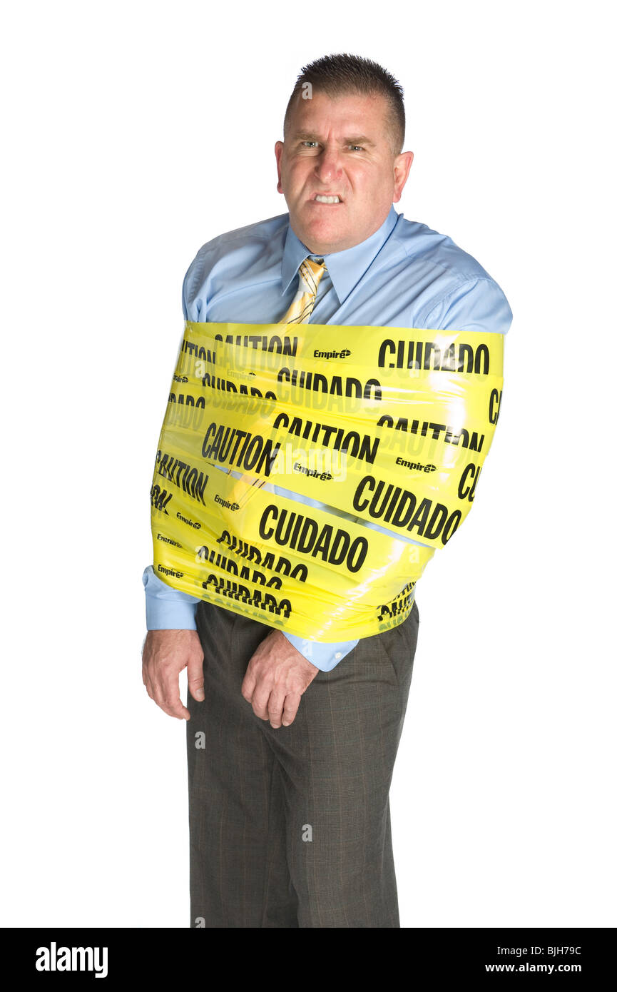 An angry businessman wrapped in caution tape as a warning to coworkers snarls as a result of stress and frustration - Stock Image