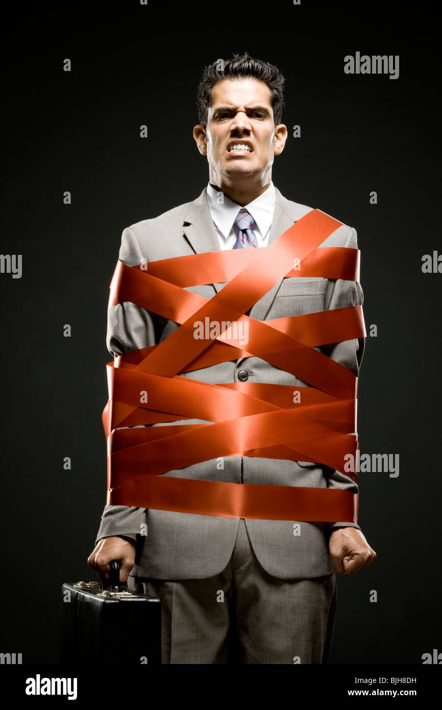 businessman wrapped up with red tape - Stock Image