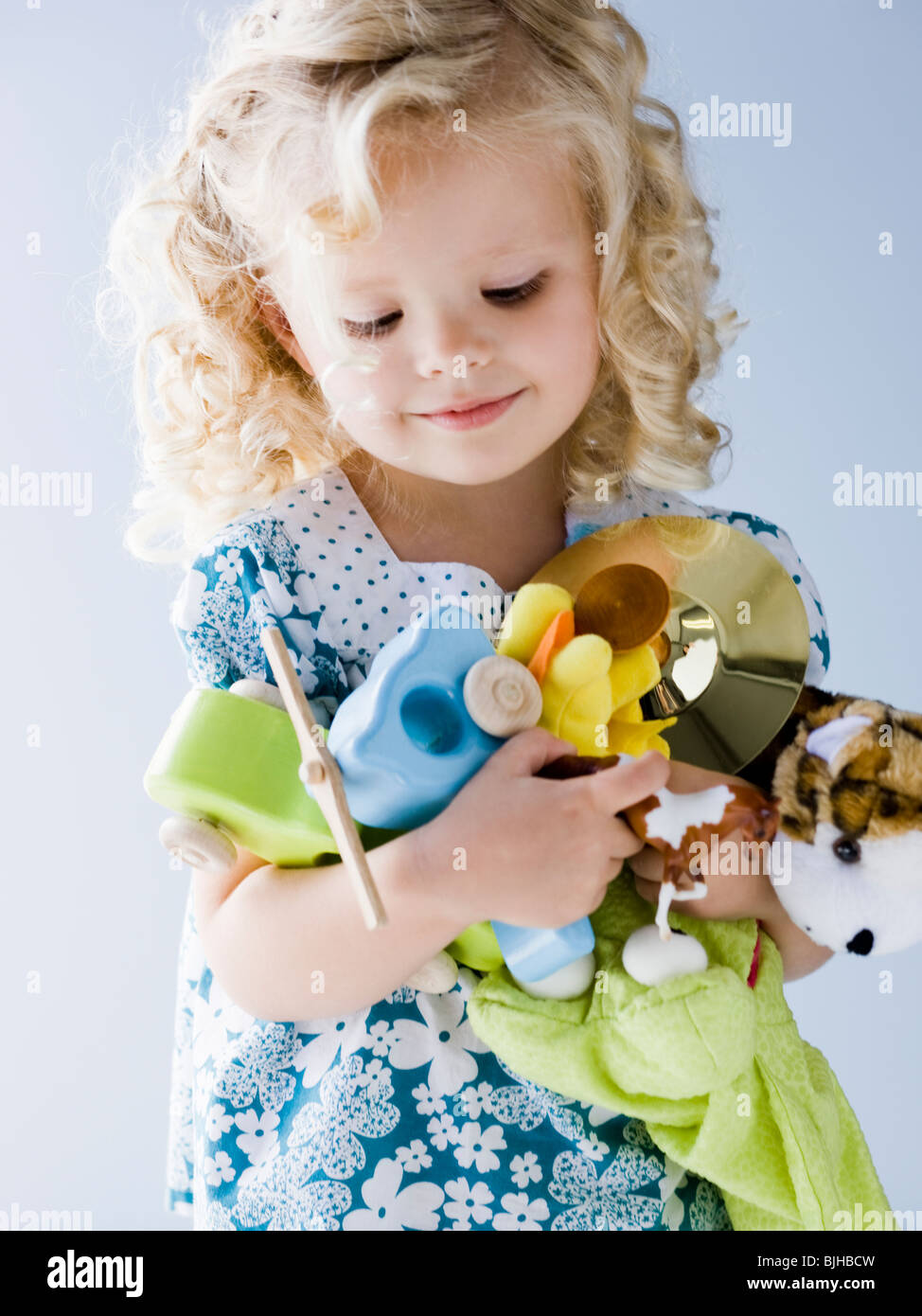 little girl holding an armful of her toys - Stock Image