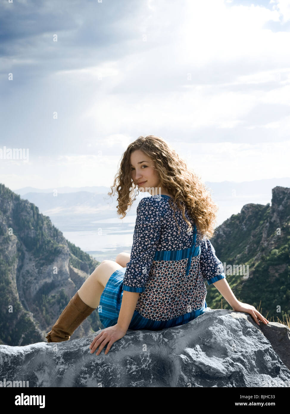 woman in a floral print dress on a mountain top sitting on a rock - Stock Image