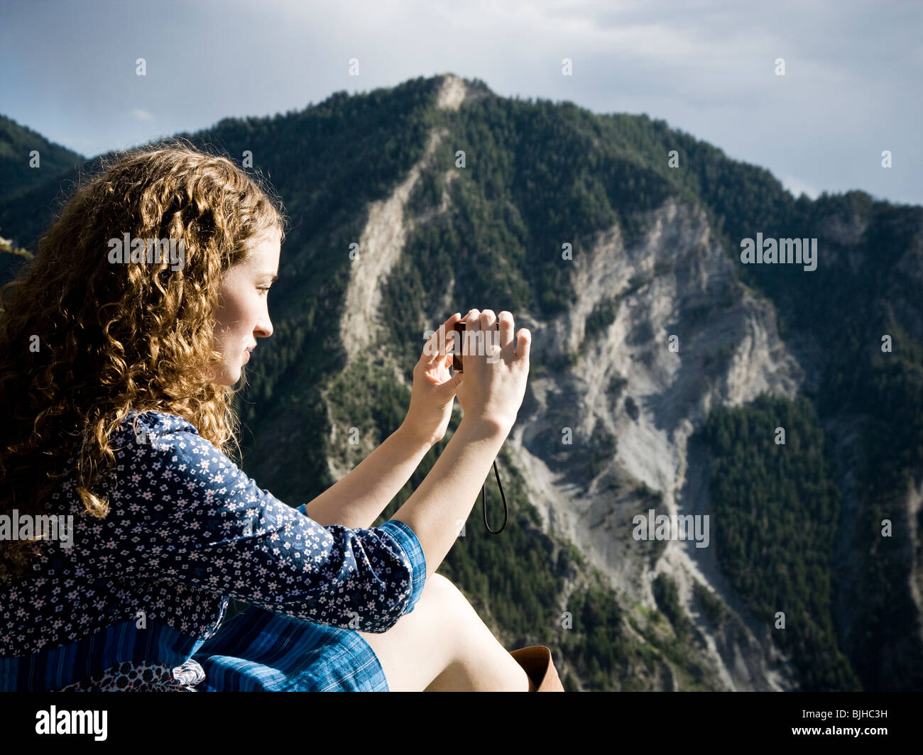 woman in a floral print dress on a mountain top - Stock Image