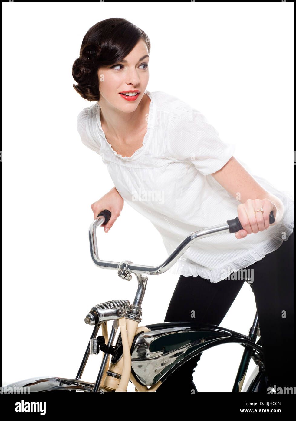 woman with her hair up in a classic hollywood hairstyle reminiscent of the 1940s riding a bike - Stock Image