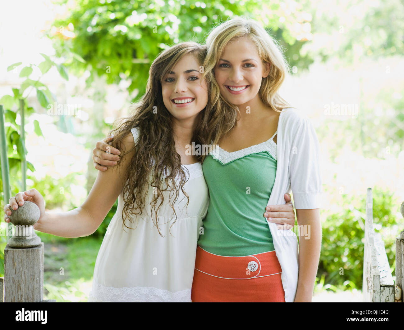 9972865382 two young women in a garden with their arms around each other Stock ...