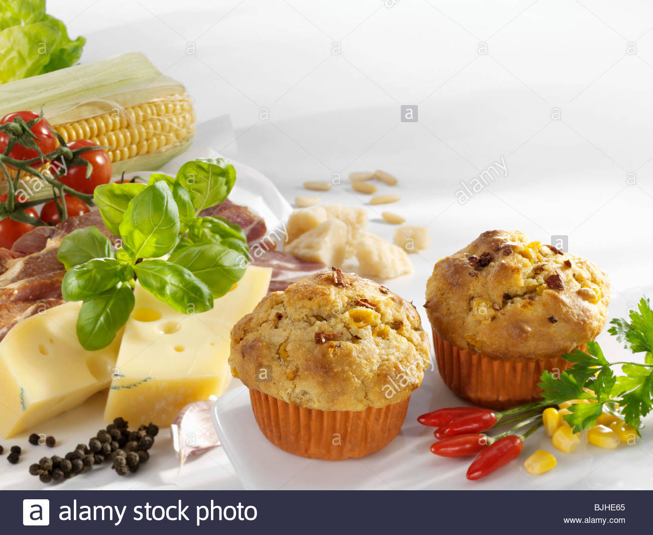 Hearty muffins, surrounded by ingredients - Stock Image
