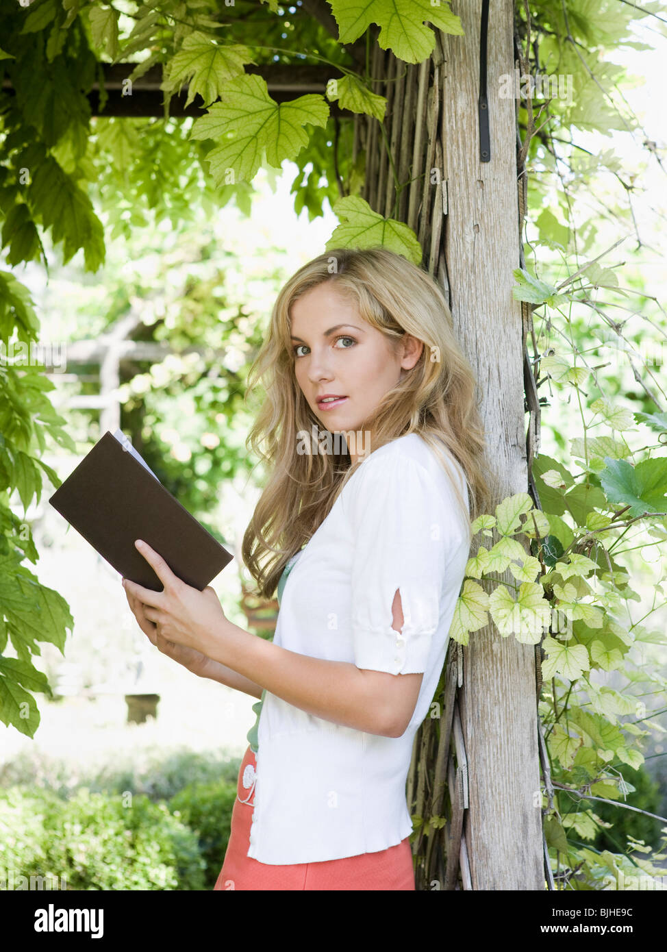 woman in the garden reading a book - Stock Image