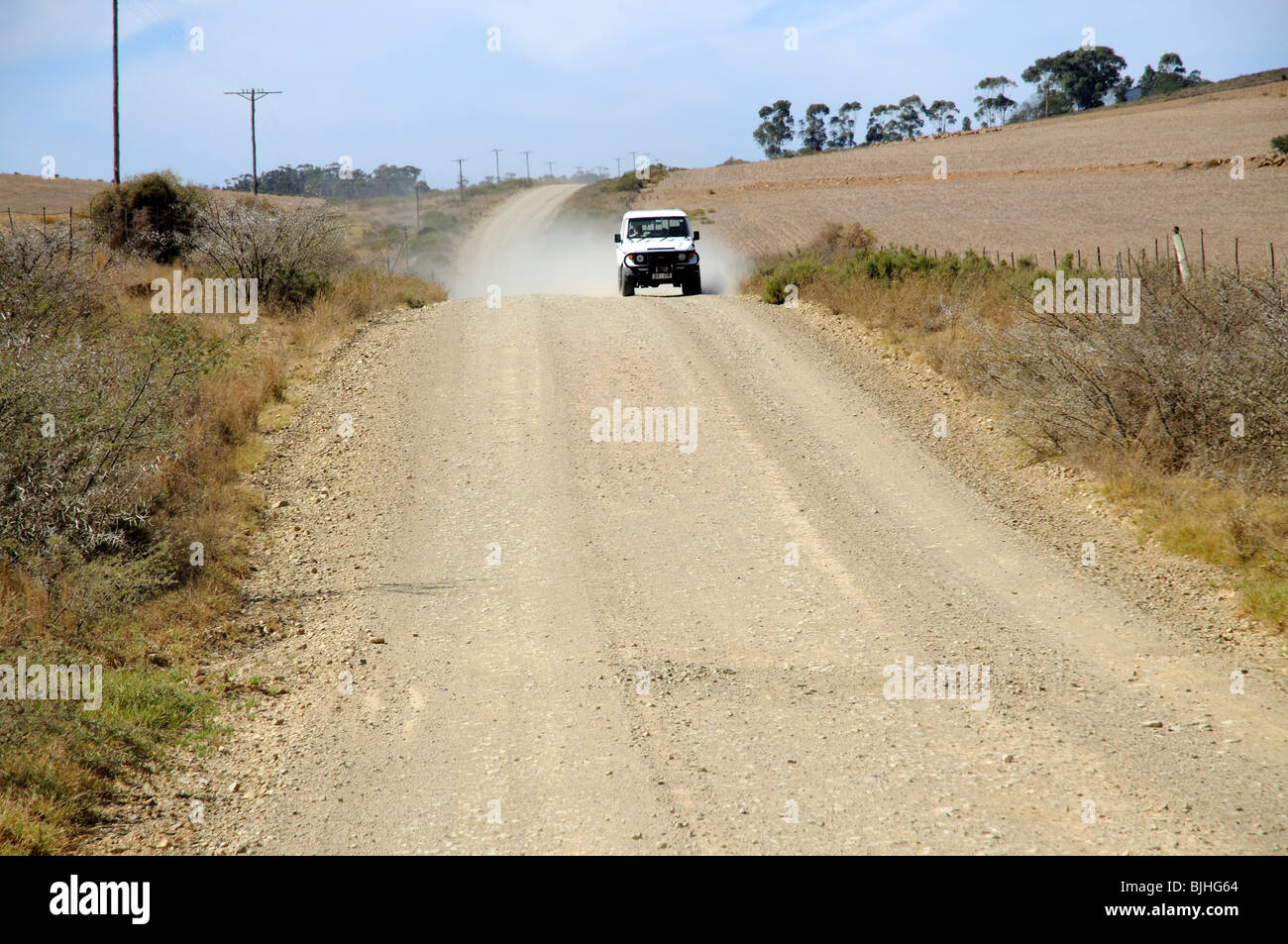 Motoring along the Garden Route. One of the may gravel roads encountered in southern Africa this Toyota drives toward - Stock Image