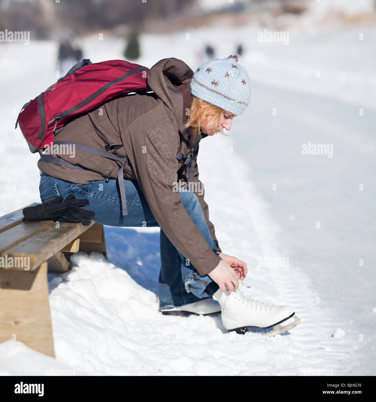 Woman lacing up her ice skates outdoors, Assiniboine River Trail, Winnipeg, Manitoba, Canada. - Stock Image