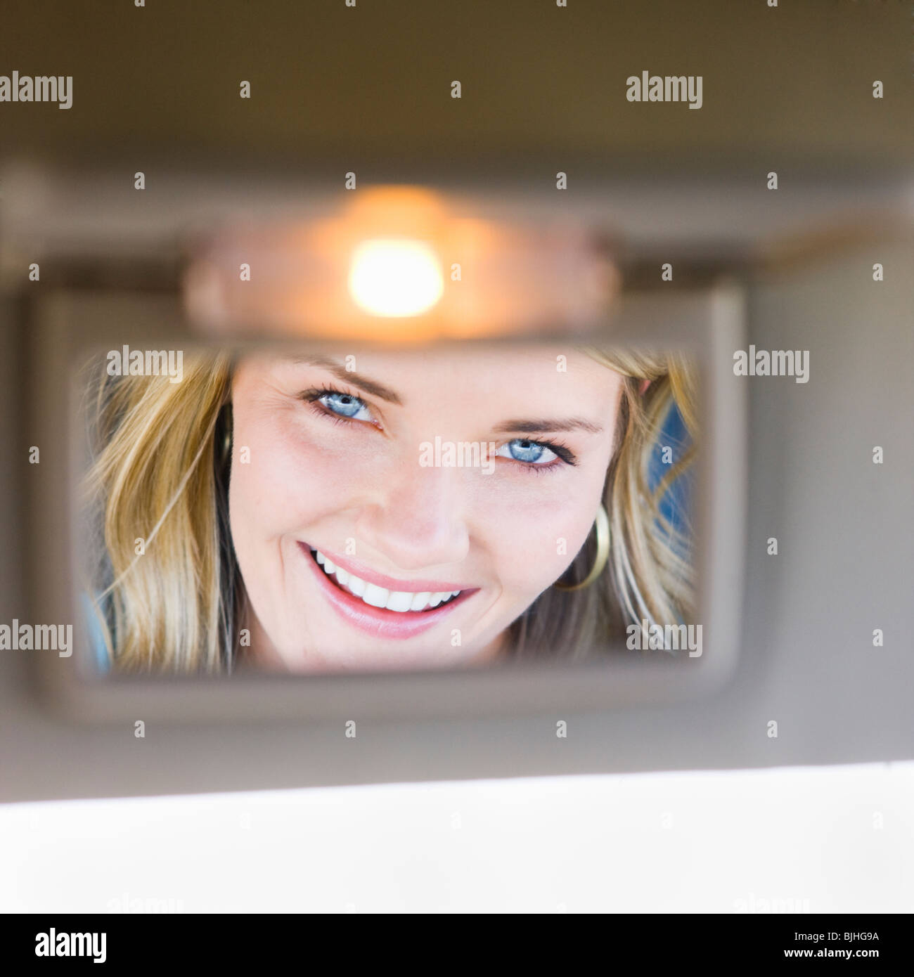 woman looking in visor mirror in car - Stock Image