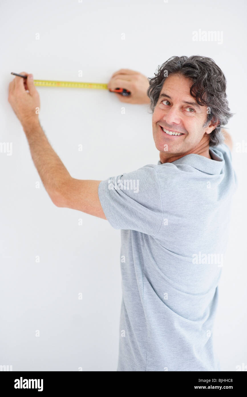 Carpenter marking straight line on wall - Stock Image