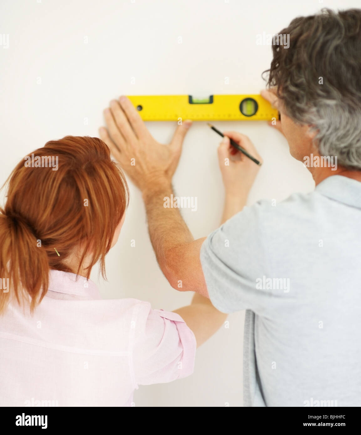 Couple marking a straight line on wall - Stock Image