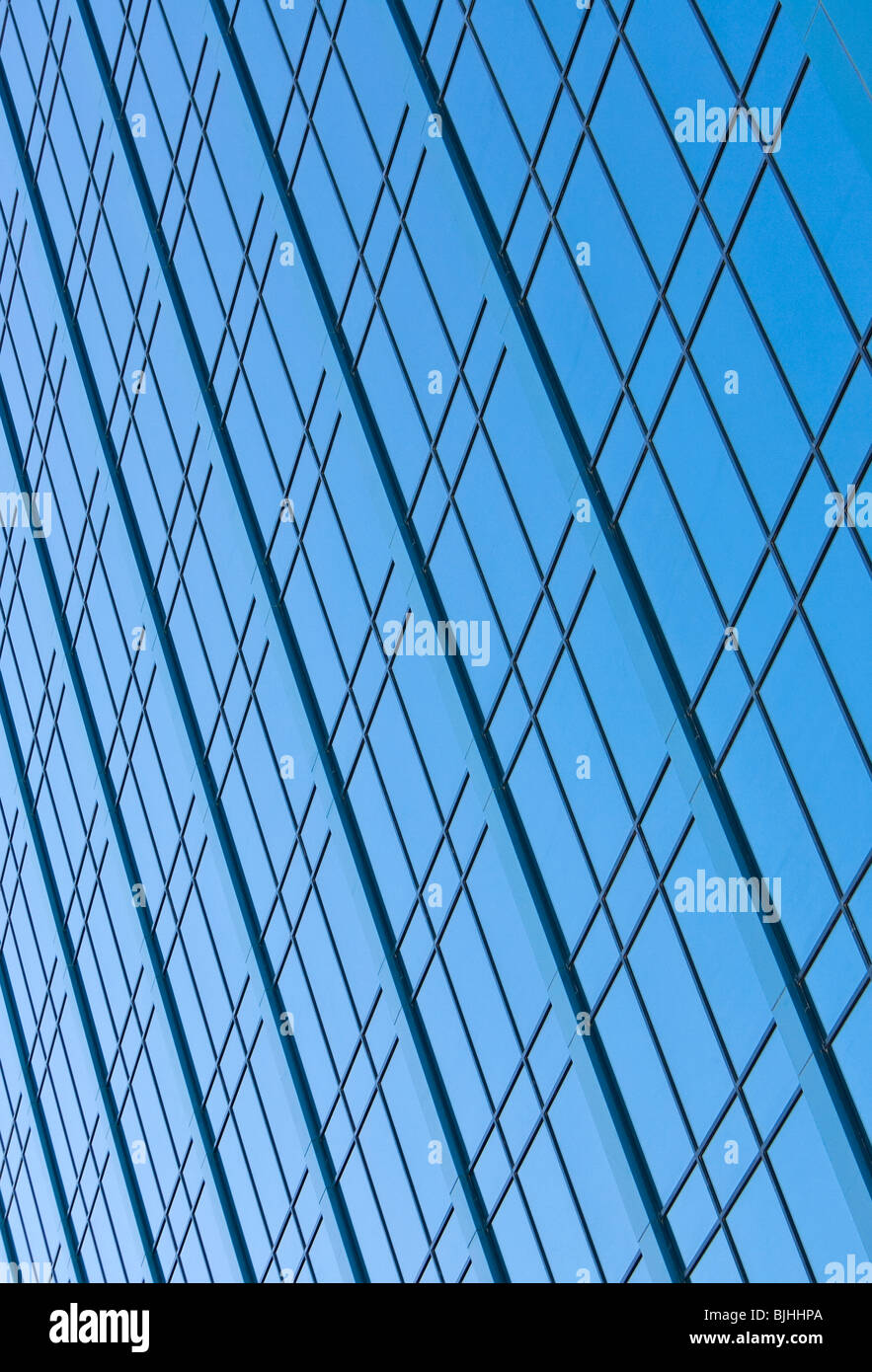 Blue sky reflecting in the windows of a modern skyscraper office block - Stock Image