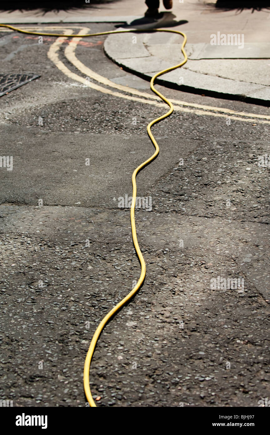 hose pipe on road - Stock Image