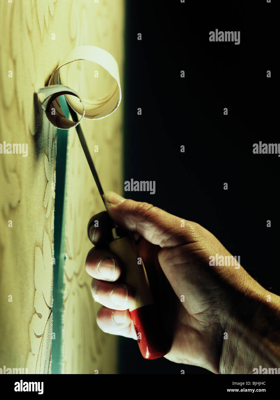 peeling wallpaper with stripping knife - Stock Image
