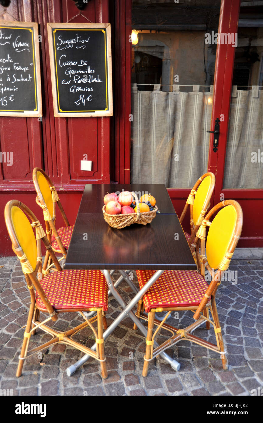 Attractive table and chairs outside a restaurant in Annecy in the Haute Savoie, Rhone Alpes region of France. Chalkboard - Stock Image