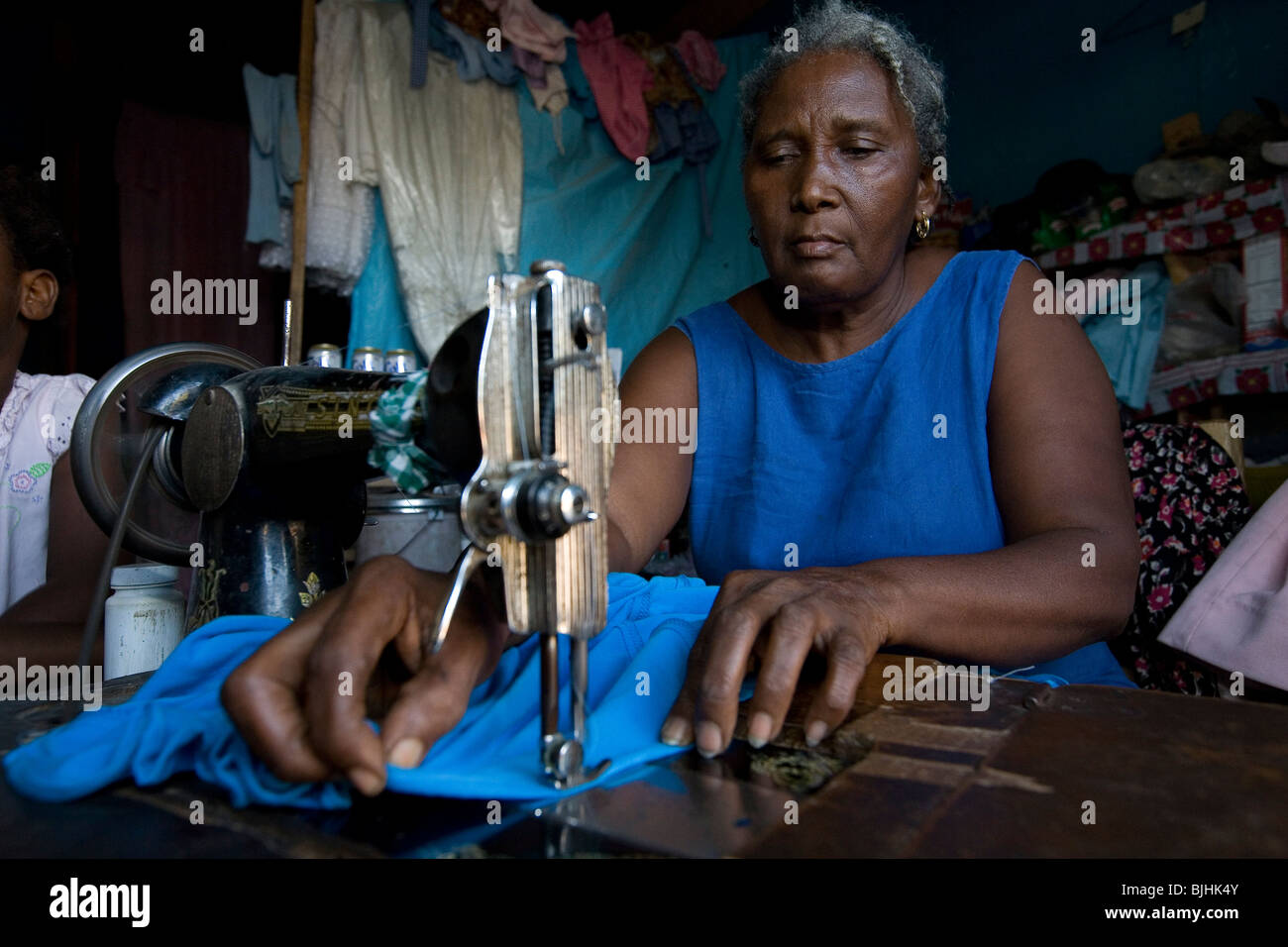 A tailor works in her alterations shop in Mirebalais, Haiti. - Stock Image
