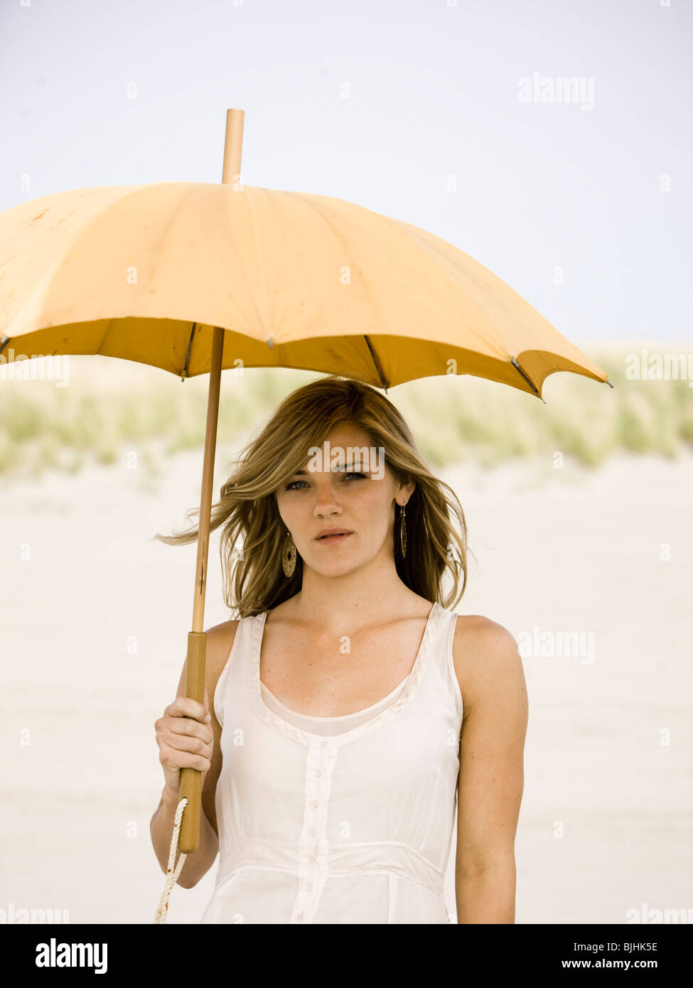 woman holding an umbrella at the beach - Stock Image