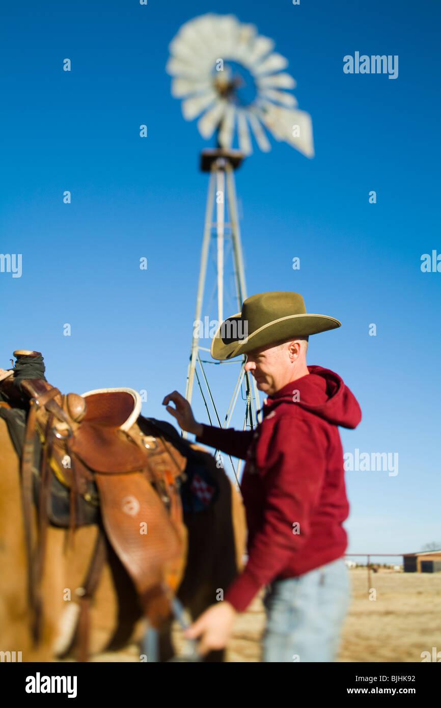 cowboy saddling up his horse - Stock Image