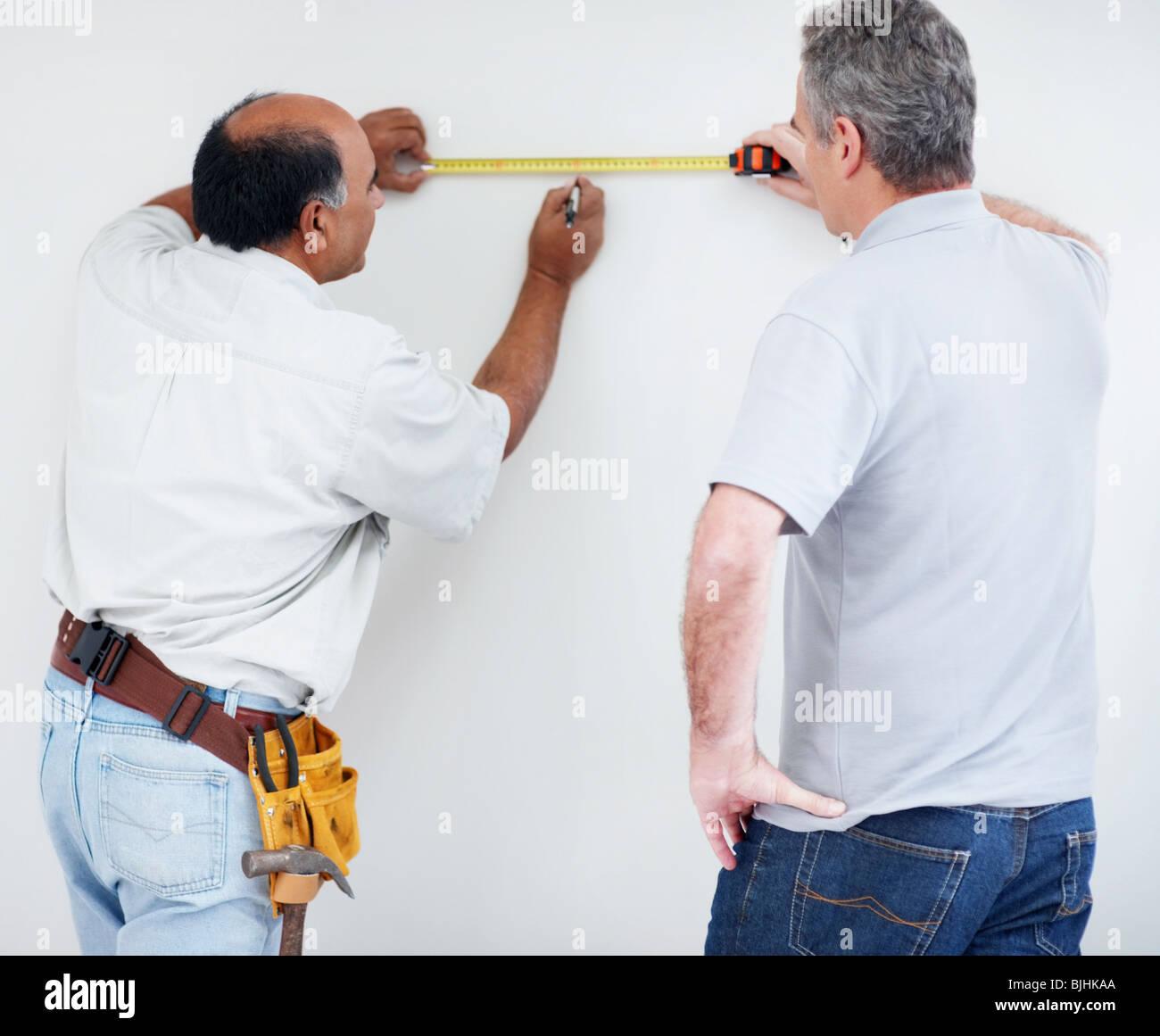 Men measuring wall Stock Photo
