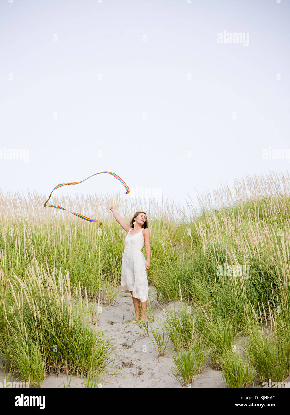 woman at the beach with her scarf blowing away in the wind as she stands on a dune covered with tall grass - Stock Image