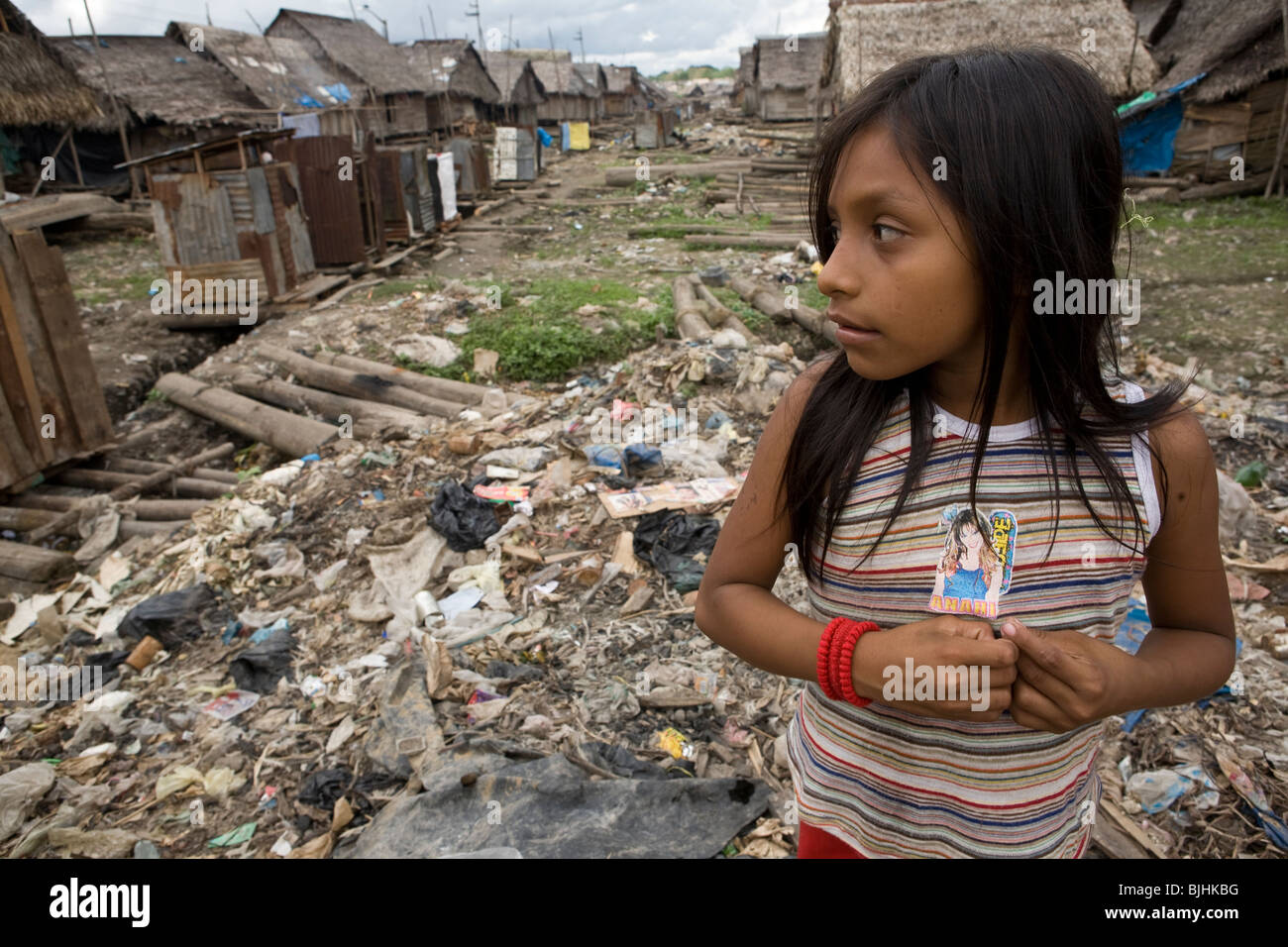 A girl stands in a garbage-strewn neighborhood in Puerto Belen, Iquitos, in Peru's Amazon Basin. - Stock Image