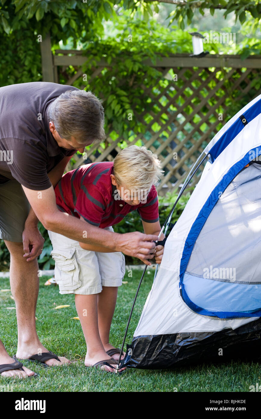father and son putting up a tent in the back yard - Stock Image