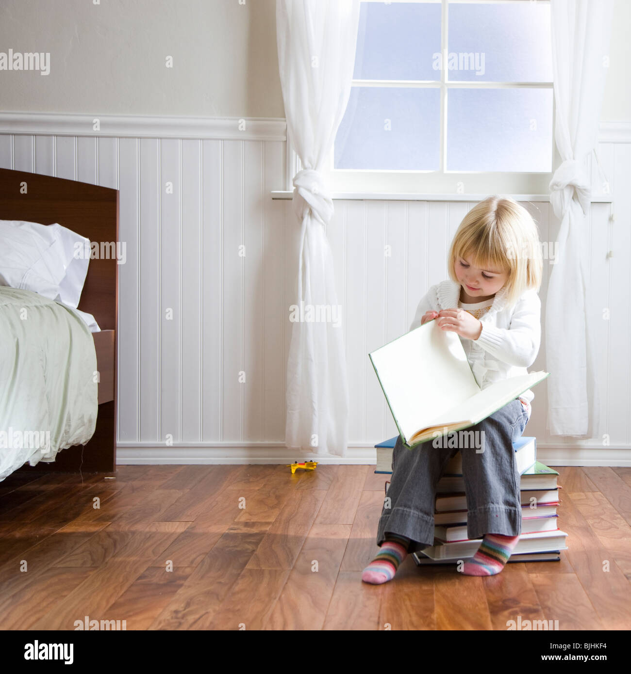 little girl reading a book while sitting on a stack of books - Stock Image