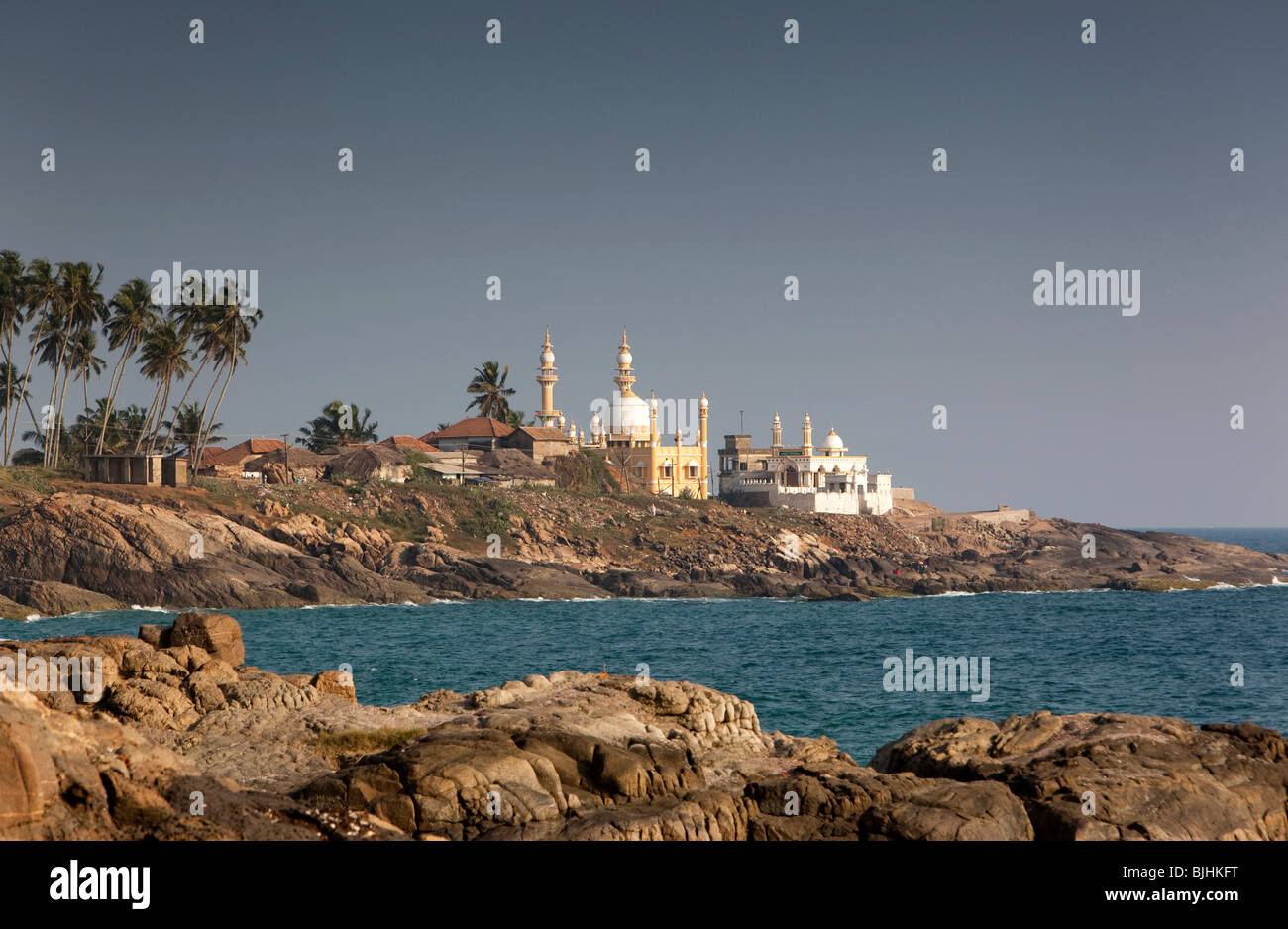India, Kerala, Kovalam, Vizhinjam village mosques across the bay from lighhouse - Stock Image