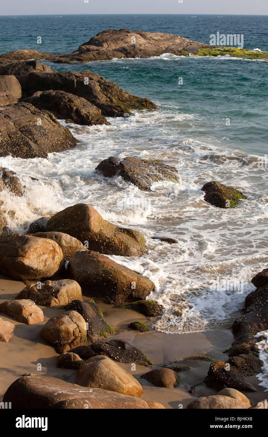 India, Kerala, Kovalam, waves rolling into secluded rocky cove - Stock Image