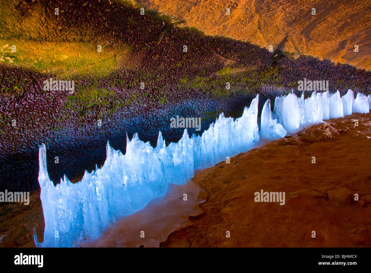 Ice forms along a spring, Arches National Park, Utah, inside large cave in winter - Stock Image