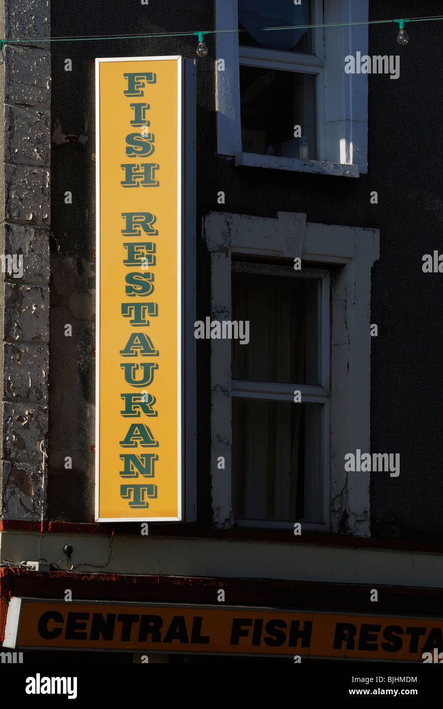 Fish restaurant sign spotlit by sunshine on a building with peeling paintwork, Aberystwyth, Wales. - Stock Image