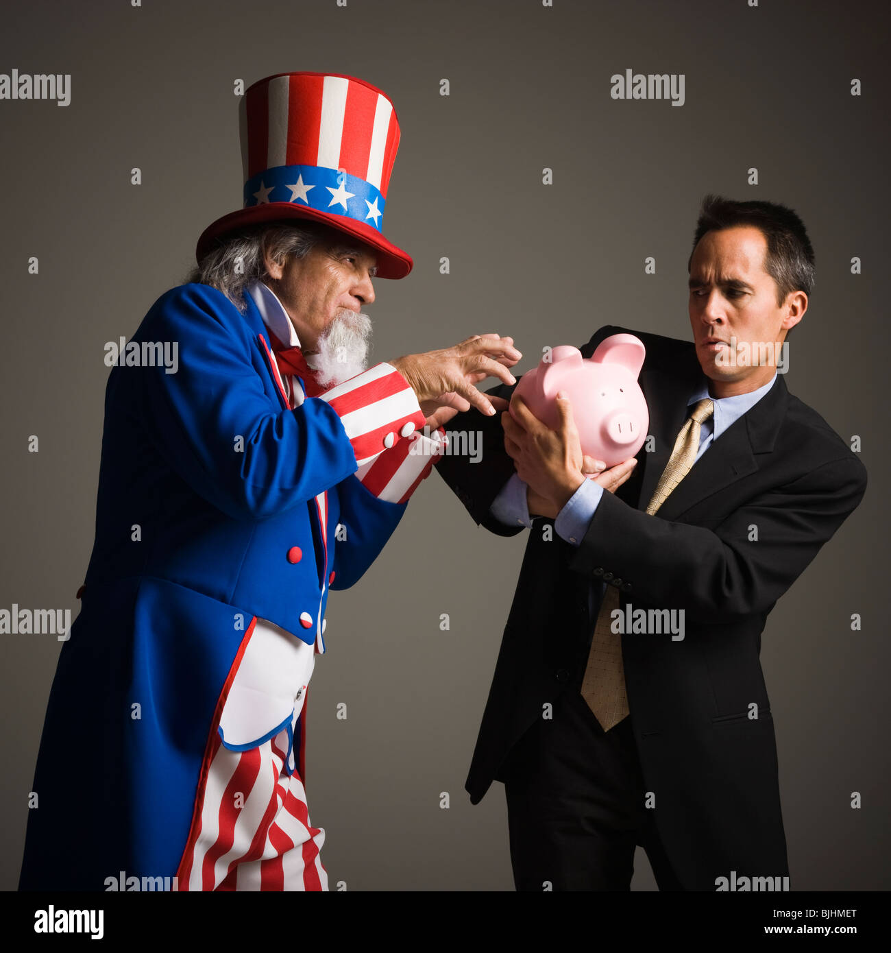 uncle same stealing a man's piggy bank - Stock Image