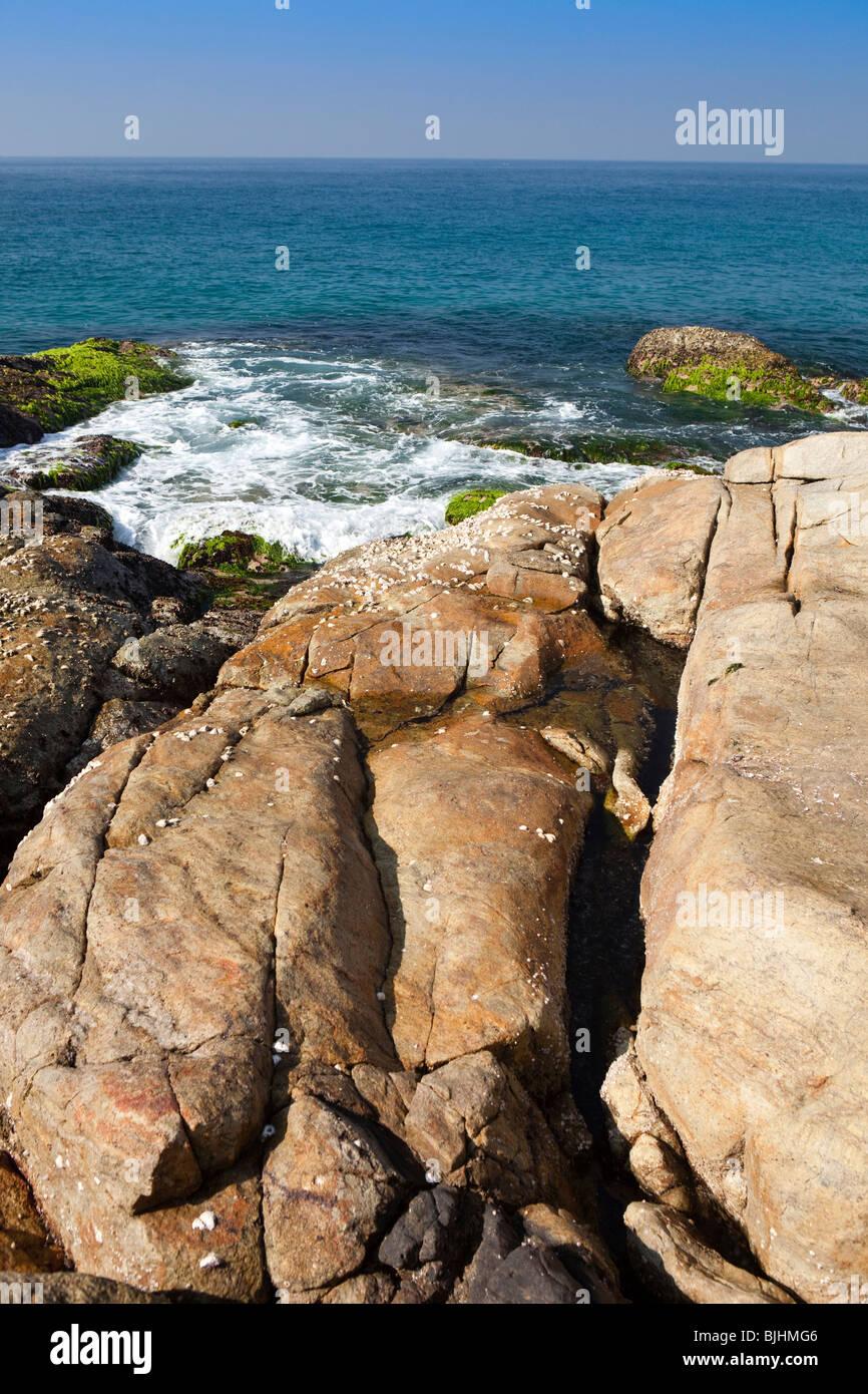 India, Kerala, Kovalam, waves rolling onto rocky headland between Vizhinjam and Lighthouse Beach - Stock Image