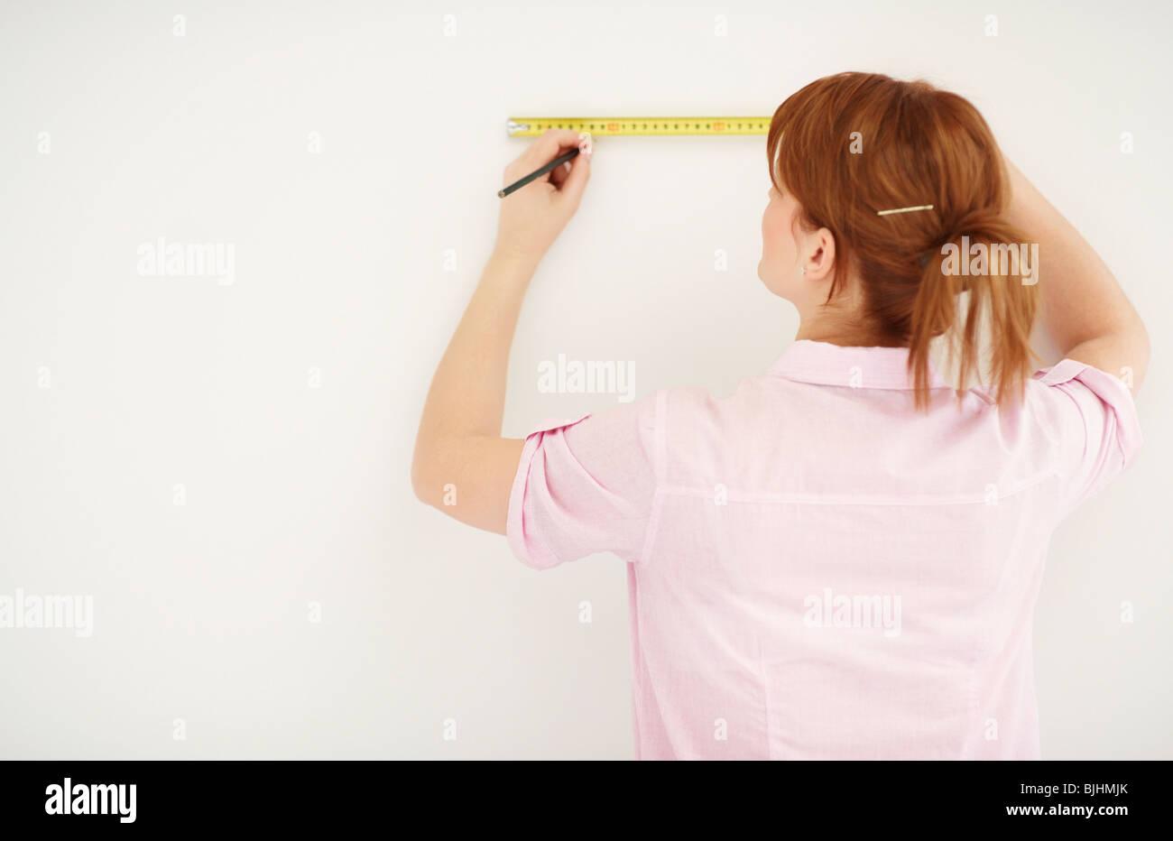 Woman using measuring tape - Stock Image