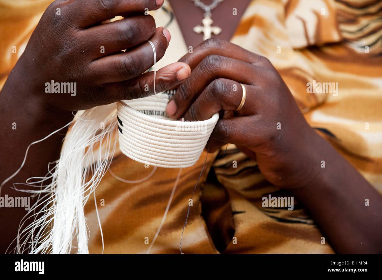 Lady weaving a traditional basket. Rwanda. - Stock Image