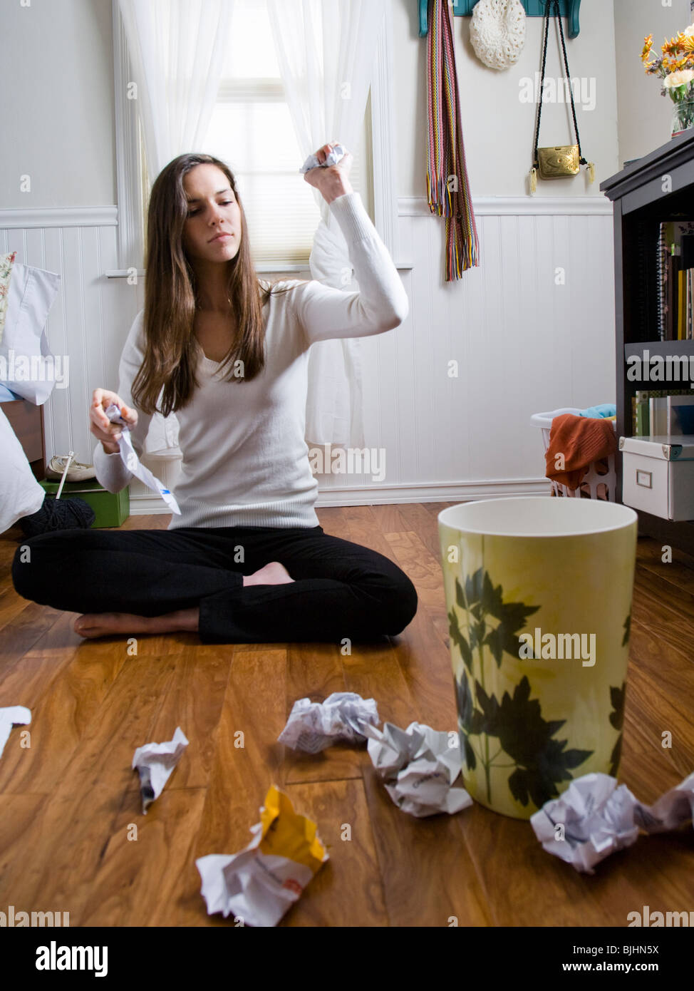 woman sitting on the floor throwing balls of paper into the wastebasket - Stock Image