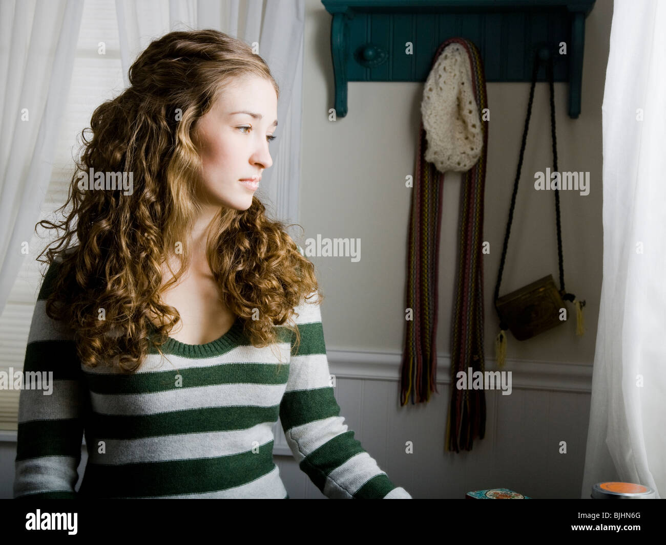 woman sitting in her bedroom next to a window - Stock Image