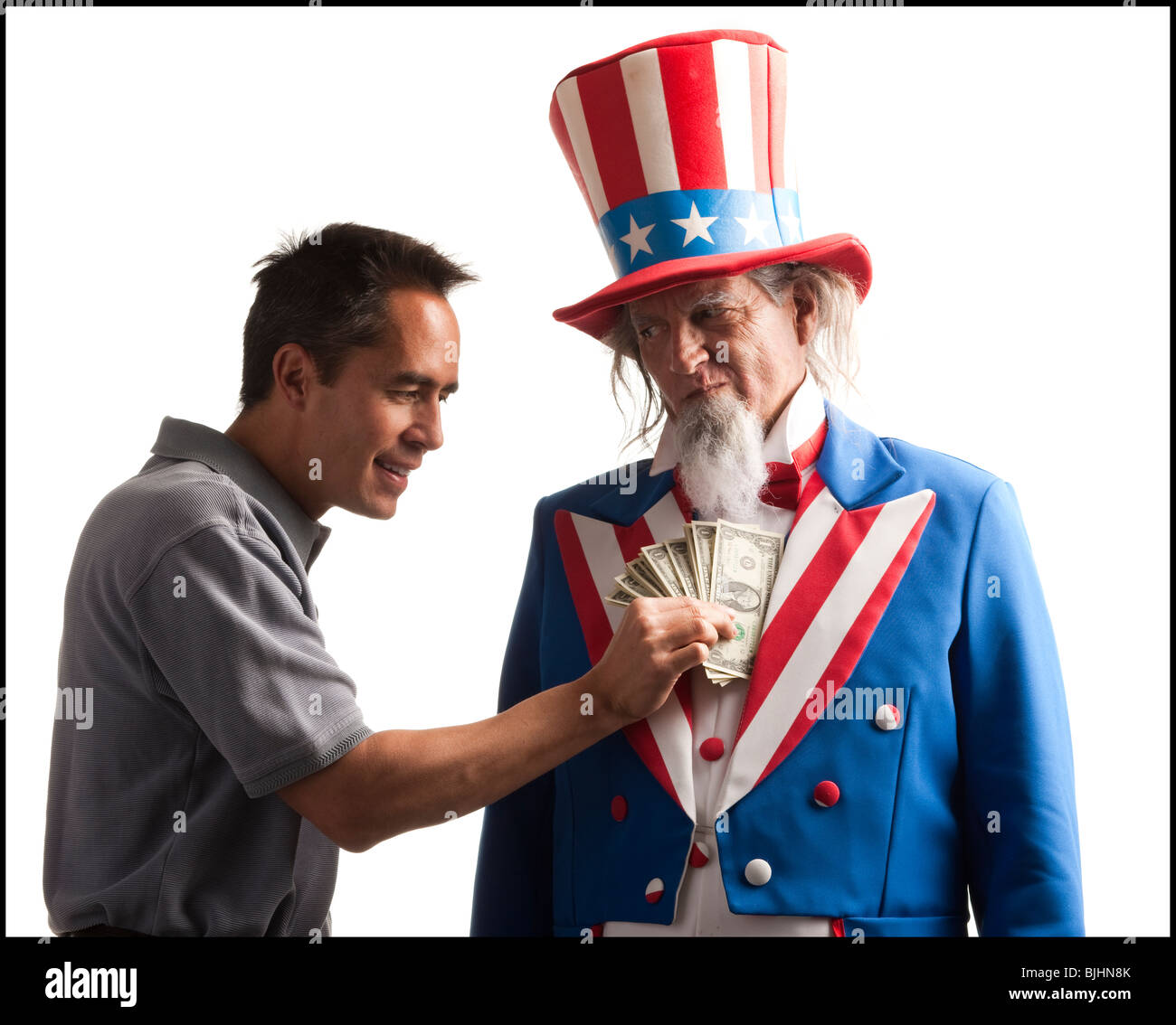 man taking money out of uncle sam's coat - Stock Image